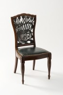 A wooden chair with four legs, a leather seat and an intricate fretwork back